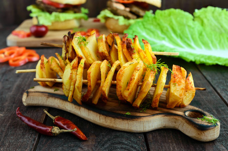 Baked potato circles on a bamboo skewer with spices (homemade chips). Snacks for beer on a dark wooden background. Close-up. Stock Photo