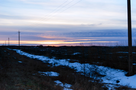 Sunset over the field, in some places covered with snow. December, Ukraine. Stock Photo