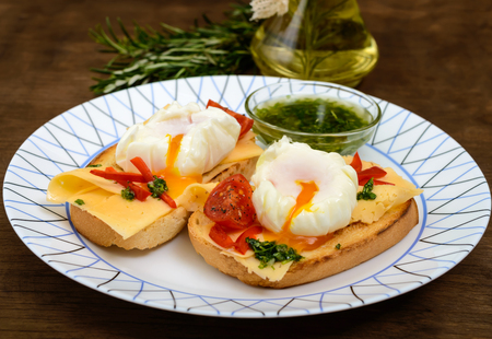Crispy toast with poached egg, cheese, peppers, tomatoes, souse on a plate on a dark wooden background. Close up