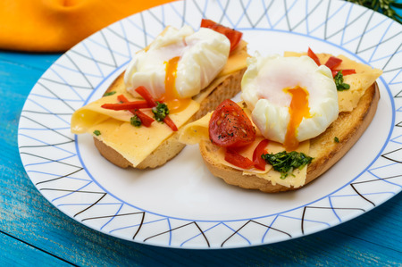 Crispy toast with poached egg, cheese, peppers, tomatoes, souse on a plate on a blue background. Close up Stock Photo