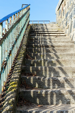 Abandoned staircase with concrete stepping stones and metal handrails, illuminated by the sun. View from the bottom up. Sunny day.