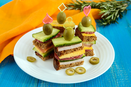 toothpick: Mini sandwiches (canape) with fresh cucumbers, ham, cheese, olives, salami, black bread on a white plate on blue background.