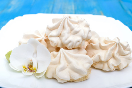 Light air vanilla meringue on a white plate with orchid flower on a blue background. Close-up. Stock Photo