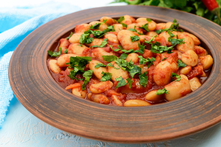 White large beans in sweet and sour tomato sauce in a clay bowl on a light background. Vegetarian cuisine. Lenten meal. Close up Stock Photo