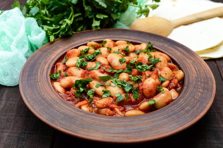 White large beans in sweet and sour tomato sauce in a clay bowl on a dark background. Vegetarian cuisine. Lenten meal.