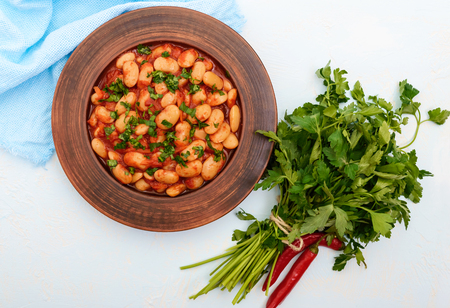White large beans in sweet and sour tomato sauce in a clay bowl on a light background. Vegetarian cuisine. Lenten meal. The top view Stock Photo