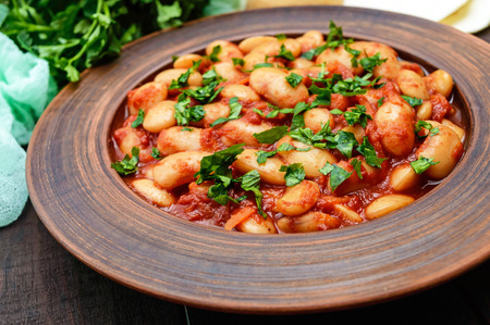 White large beans in sweet and sour tomato sauce in a clay bowl on a dark background. Vegetarian cuisine. Lenten meal. Close up