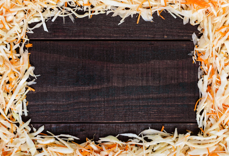 Frame made of salad. Fresh chopped cabbage and carrots. In the middle of a dark wooden space for your notes. Healthy food concept. Lenten menu.