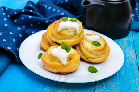 Freshly baked, cottage cheese buns, with cream and mint leaves on a white plate on a blue background.