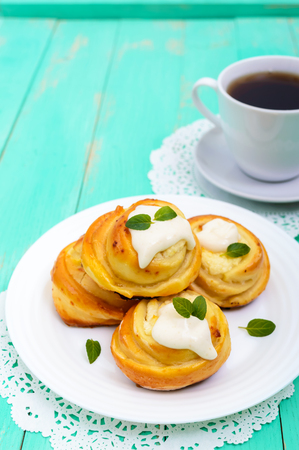 Freshly baked, cottage cheese buns, with cream and mint leaves and cup of tea on a white plate on a light background. Vertical view