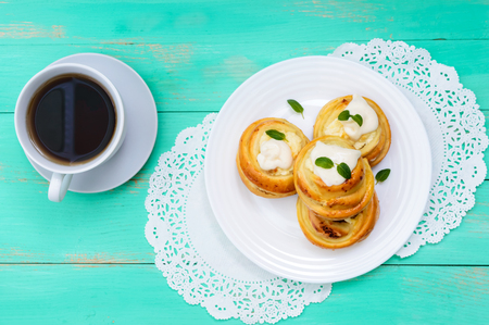 Freshly baked, cottage cheese buns, with cream and mint leaves and cup of tea on a white plate on a light background. The top view Stock Photo