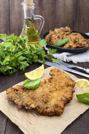 Homemade Vienna schnitzel on the wooden background. A traditional dish of Austrian cuisine. Vertical view