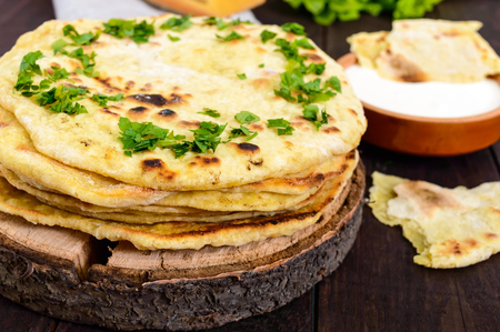 Thin flatbread - traditional Asian bread on a dark wooden background.