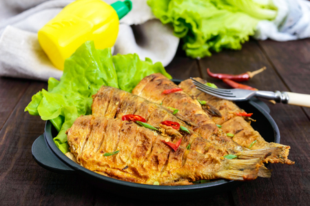 Fried fish carp (sazan) on a cast-iron frying pan with lettuce leaves on a dark wooden background.