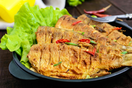 Fried fish carp (sazan) on a cast-iron frying pan with lettuce leaves on a dark wooden background. Close up