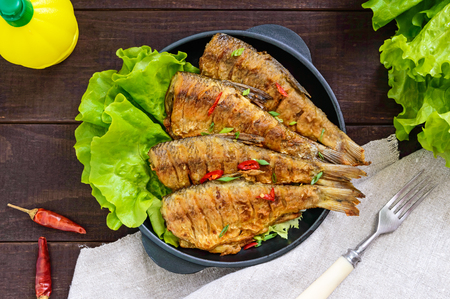 Fried fish carp (sazan) on a cast-iron frying pan with lettuce leaves on a dark wooden background. The top view.