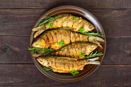 Fried fish carp (sazan) on a ceramic bowl with branches of rosemary on a dark wooden background. The top view.