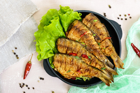Fried fish carp (sazan) on a cast-iron frying pan with lettuce leaves on a light background. The top view.