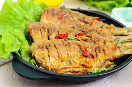 Fried fish carp (sazan) on a cast-iron frying pan with lettuce leaves on a light background. Close up