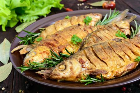Fried fish carp (sazan) on a ceramic bowl with branches of rosemary on a dark wooden background. Close up
