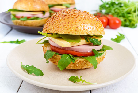 Burgers with sausage, cheese, tomato, arugula and soft bun with sesame seeds on a white wooden background. Stock Photo