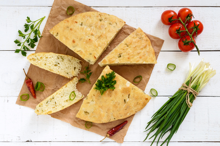 A thick flapjack - pita bread with greens (onion) on a white wooden background. A traditional Asian dish. The top view