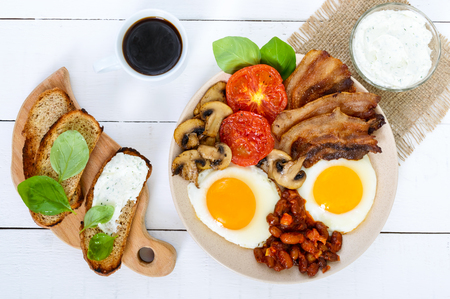 English breakfast: eggs, bacon, beans in tomato sauce, mushrooms, tomatoes, toast with cream cheese and a cup of coffee on a white wooden background. A traditional British dish. Top view.