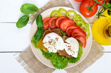 Sandwich with egg poached, lettuce, black bread with seeds, tomatoes, sweet pepper on a plate on a white wooden table. The top view