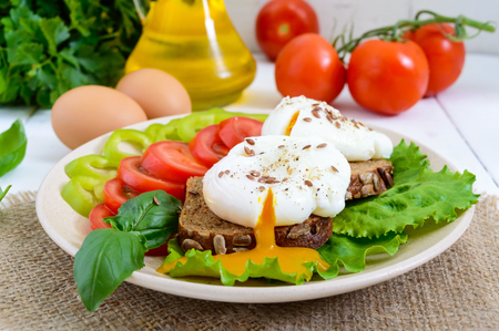 Sandwich with egg poached, lettuce, black bread with seeds, tomatoes, sweet pepper on a plate on a white wooden table.