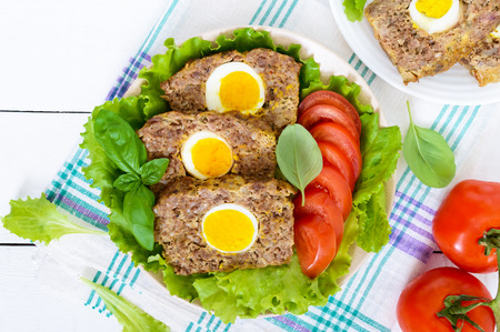 meatloaf: Meatloaf stuffed boiled egg with fresh tomato and lettuce leaves on a plate on a white wooden table.