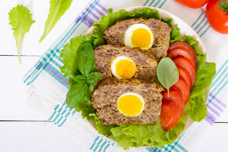 meatloaf: Meatloaf stuffed boiled egg with fresh tomato and lettuce leaves on a plate on a white wooden table. Top view. Close-up. Stock Photo