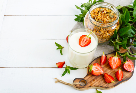 Yogurt, fresh ripe strawberry, granola - dietary dish on a white wooden table. Proper nutrition. Healthy breakfast.