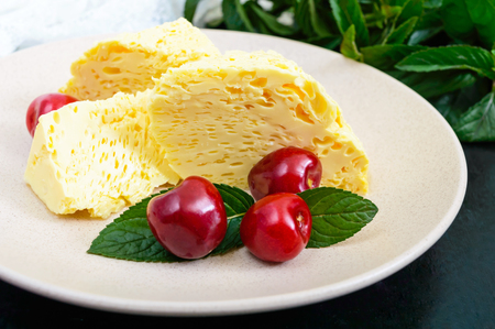 Air milky-vanilla pudding with ripe cherries and mint leaves on a plate. Dessert of Brazilian cuisine.