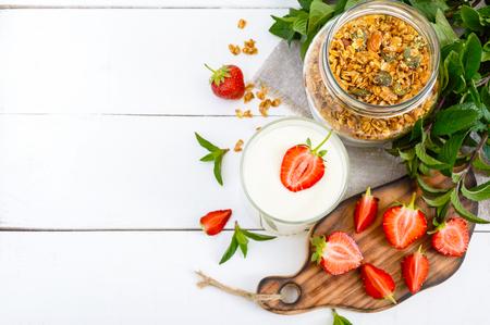 ヨーグルト、新鮮な熟したイチゴ、グラノーラ - 白い木製のテーブルの食事の料理。適切な栄養。健康的な朝食。 写真素材