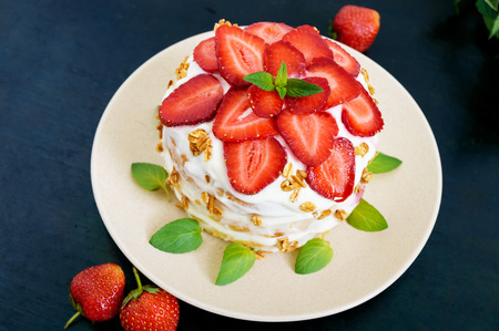 mascarpone: A festive cake with fresh strawberries, cream, decorated with mint leaves on a black background. Top view. Stock Photo