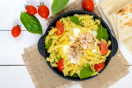 Fusilli pasta, fried eggs and tomatoes. Serve on a cast-iron frying pan on a white wooden background. Top view. Stock Photo