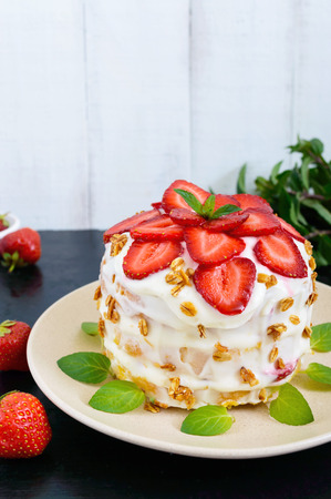 mascarpone: A festive cake with fresh strawberries, cream, decorated with mint leaves on a black background. Vertical view