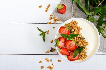 栄養フィットネス朝食のボウル: ヨーグルト、グラノーラ、新鮮なイチゴ、木製白地にミント。適切な栄養。平面図です。