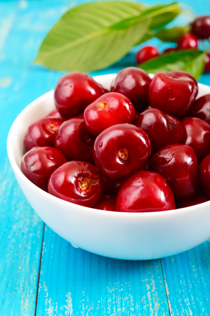 Ripe red cherry berries in a white ceramic bowl on a blue wooden background. Vertical view Stock Photo