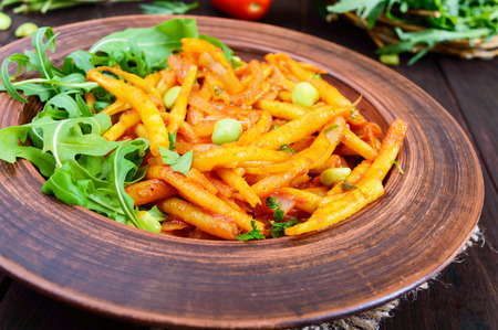 Salad from green beans, stewed with onions in tomato sauce and green leaves of arugula in a ceramic bowl on a dark wooden background.  Belgian cuisine. Vegan dish.