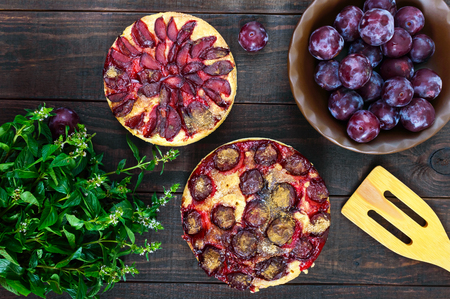 Plum pies on a dark wooden background. American traditional pastries.