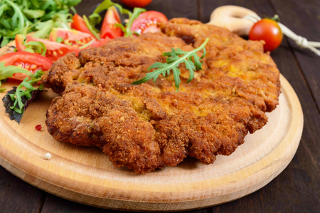 A large Viennese schnitzel  and tomato salad on a cutting board on a dark wooden background. Close up