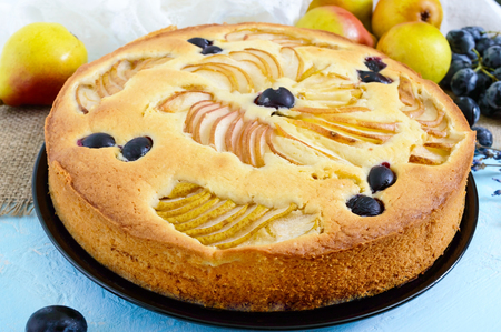 Autumn pie with pears and grapes on a light background.