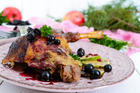 Baked goose leg in berry sauce on a ceramic plate on a white wooden background.