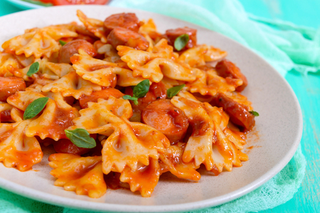 Farfalle pasta with chunks of sausage in tomato sauce on a bright background.