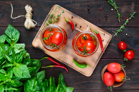 Sour tomatoes in a glass jar on a dark wooden background. Pickles. The top view
