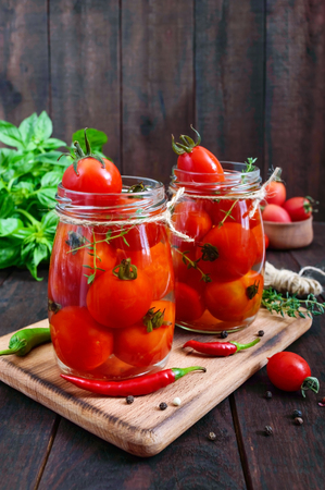 Sour tomatoes in a glass jar on a dark wooden background. Pickles. Stock Photo