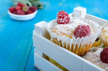 Curd cakes (muffins) with raspberries, decorated with powdered sugar. Serve in a white wooden box. Fresh raspberries in a ceramic bowl.