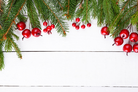 New Years, Christmas theme. Green fir branches, decorative berries on white wooden background. Celebratory background. Free space for inscriptions, notes.