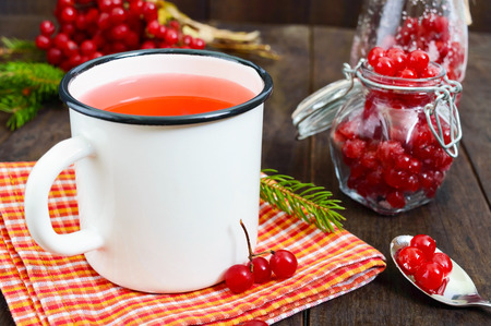 Hot berry tea in a white mug on a dark wooden background. Tea with viburnum. Berries with sugar in a glass jar. Therapeutic drink. Stock Photo